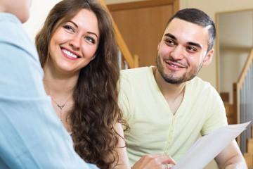 גבר צעיר ואישה צעירה יושבים ומחייכים כלפי גבר מחויט עם מסמך ביד