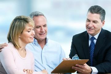איש מבוגר ובת זוגתו חותמים על מסמך שאיש עם חליפה מציג להם