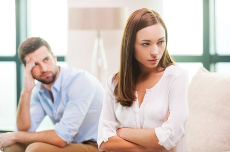 34798855 - relationship difficulties. depressed young woman keeping arms crossed and looking away while man sitting behind her on the couch