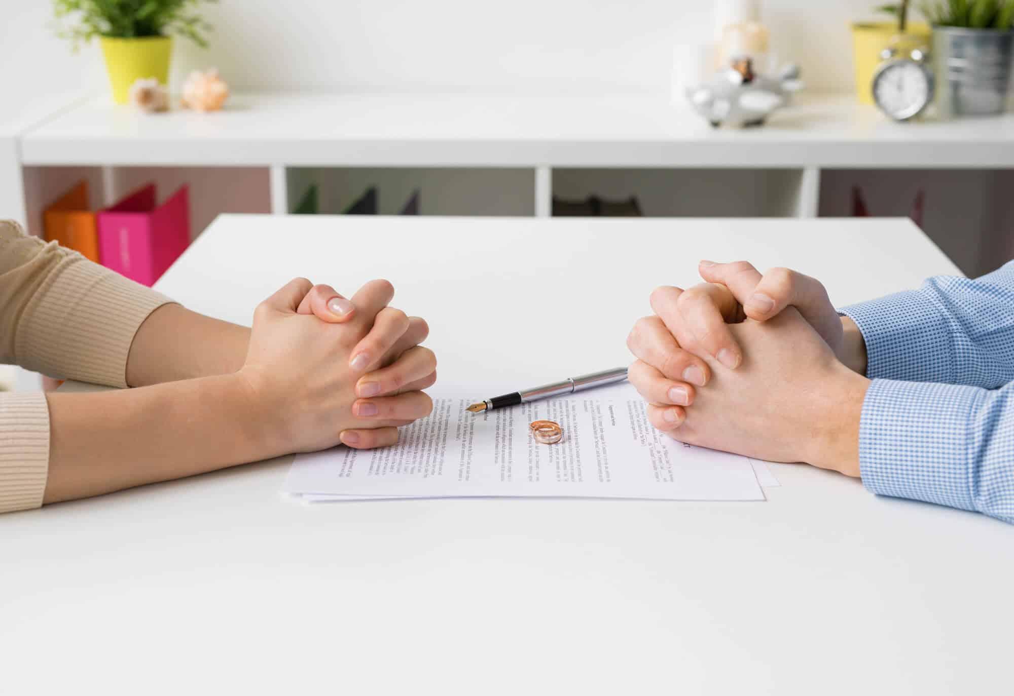 גבר ואישה יושבים זה מול זה כאשר טבעות הנישואין שלהם על מסמך לבן דמוי חוזה